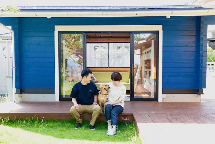 青い壁の前のウッドデッキに座っている男女と中型犬