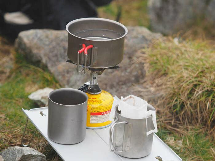 登山でバーナーを使ってコーヒーを作っている画像