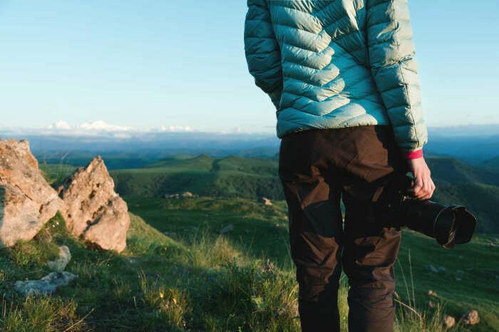 ダウンパーカを着て山の頂上から景色を見ている人の画像