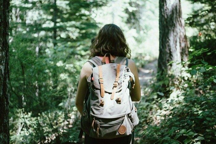 リュックを背負ってハイキングしている女性