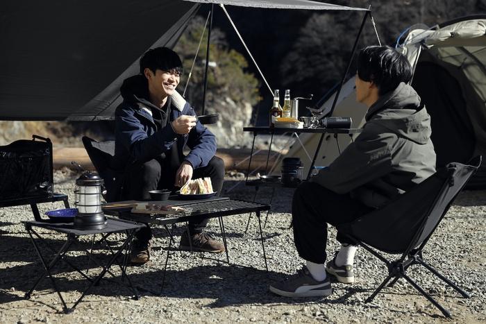 キャンプサイトで談笑する男性