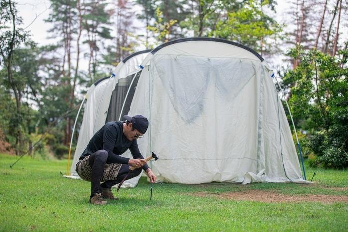 テント設営でペグをハンマーで打つ男性