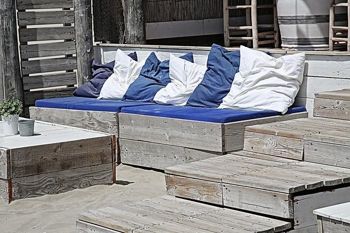 屋外の気の台に上に並べられた青と白のクッション数個