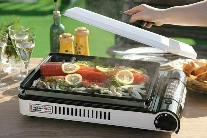 カセットコンロに鮭やキノコの具材を並べ屋外で焼いている