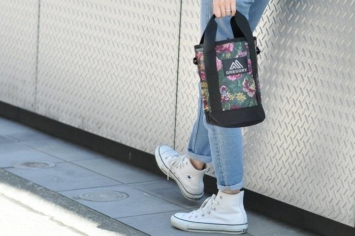 グレゴリーのランタンショルダーバッグを手に持つ女性