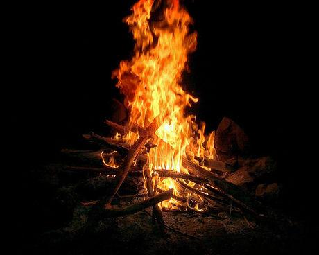 キャンプファイヤーで焚き火をしている写真