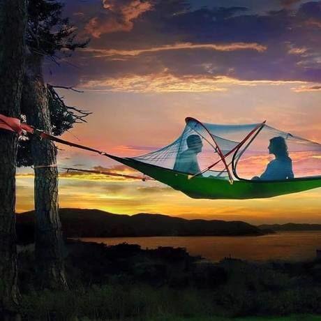 夕暮れ時のハンモックテントの中の男女