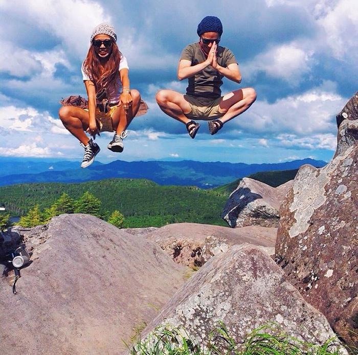 岩の上でジャンプをする男女