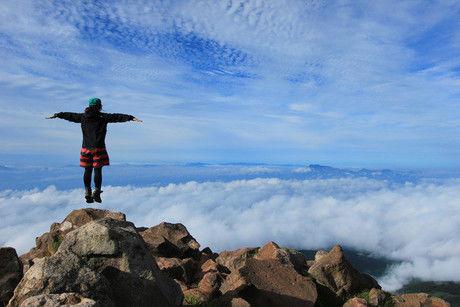 山の頂上で腕を広げジャンプする人