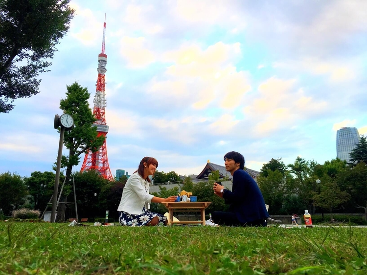 芝公園でカップルでピクニックをする様子