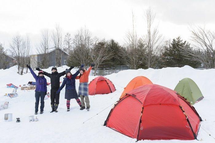雪の上に張ったテントの前でバンザイしている4人組