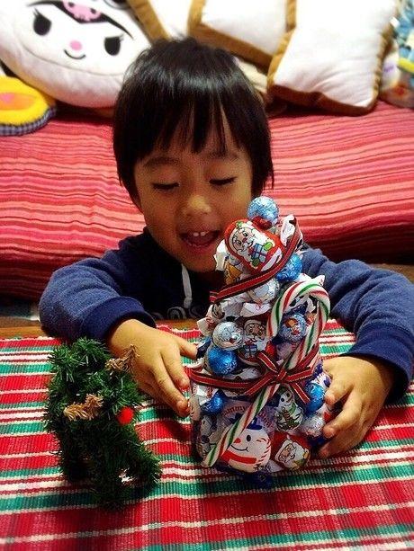 お菓子のクリスマスツリーを触る子供