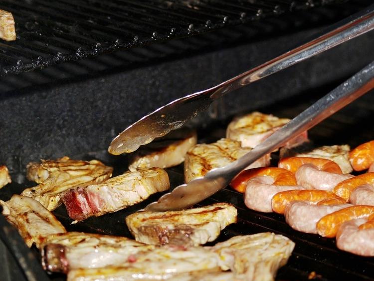 BBQでトングを使って肉を裏返す様子