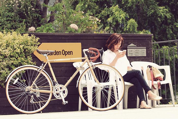 自転車と椅子に座りスマートフォンを触る女性
