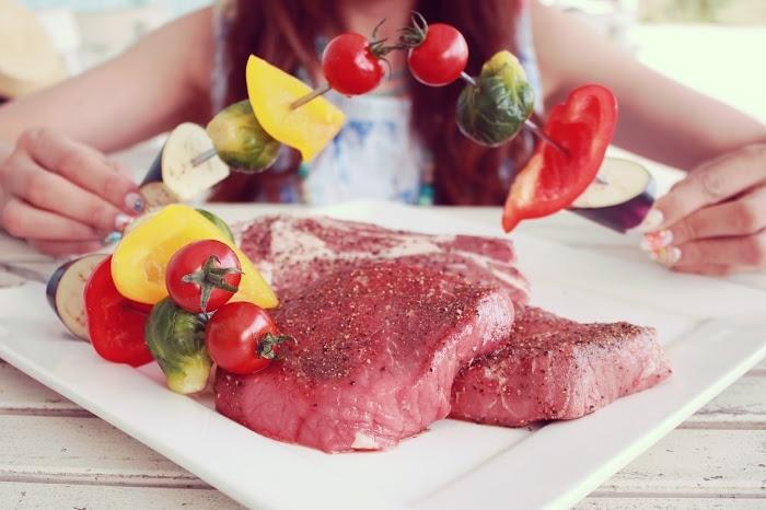 ステーキ肉と串に刺した野菜を持つ女の子の手元