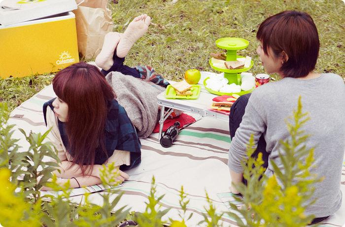 ピクニックラグの上でくつろぐ女性
