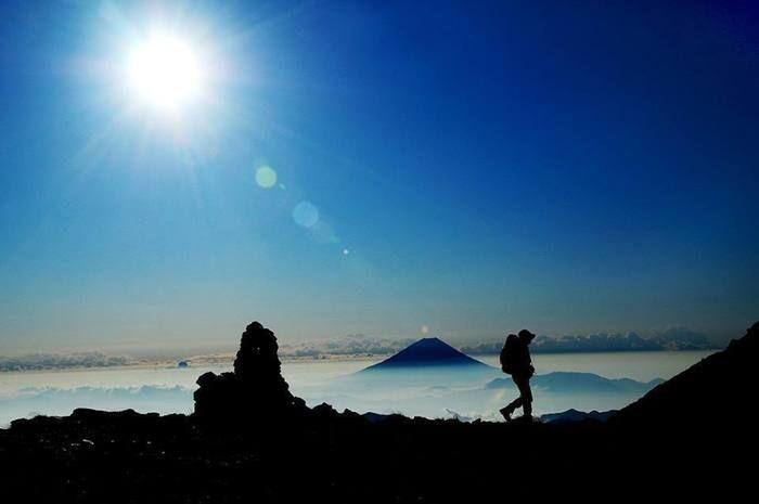 山頂付近で雲を見下ろしながら登山する人