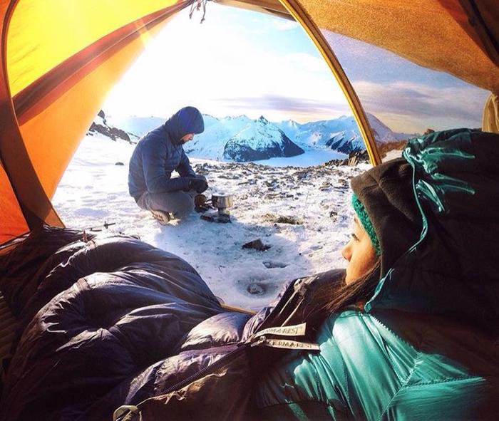 Therm-a-Rest(サーマレスト)のシュラフを見てテント外を見る女性とテント外で調理をする男性