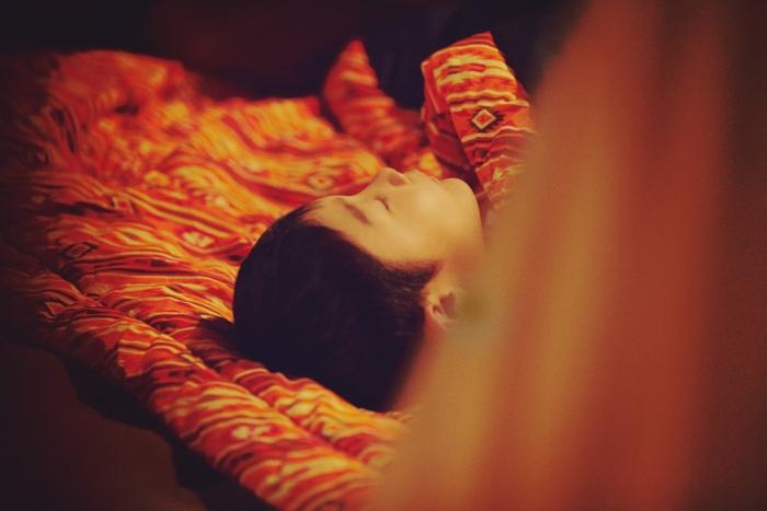 シュラフで寝る男の子