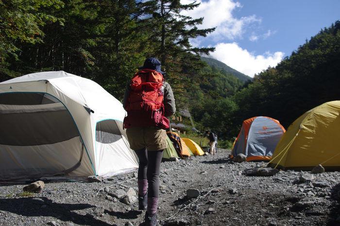 モンベルのリュックを背負ってキャンプ場を歩く人