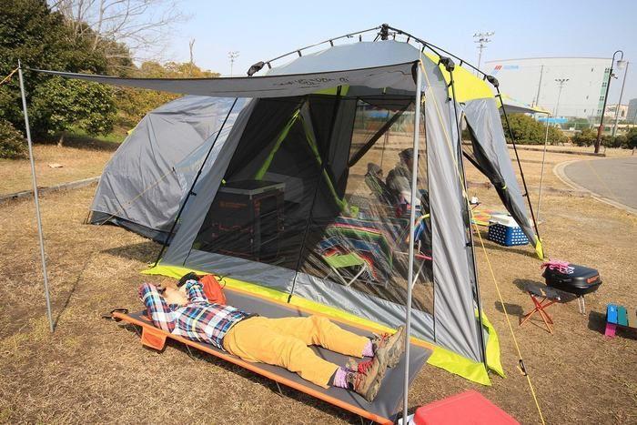 テントの横でコットに寝そべる男性