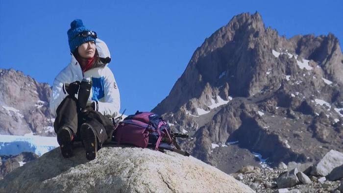 岩に座っている女性