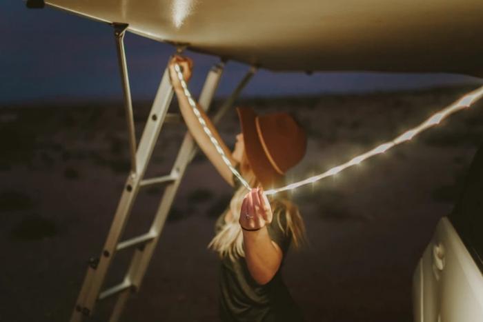 屋根にロープライトを吊り下げる様子