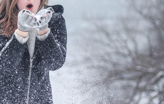 雪に息を吹きかけている女性の写真
