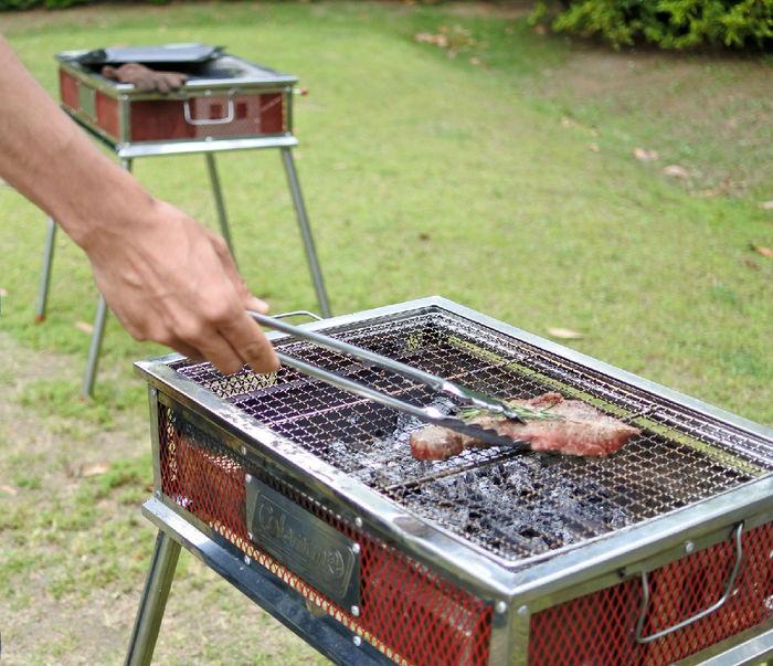 コールマンのバーベキューグリルで肉を焼く様子