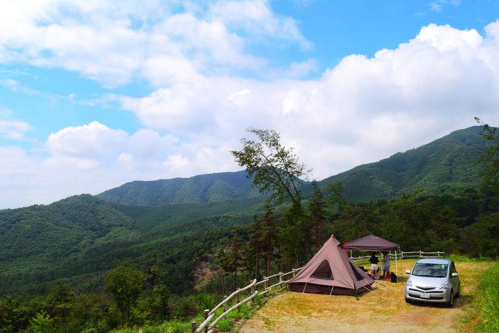 ほったらかし温泉のキャンプ場と周りの山々と青空
