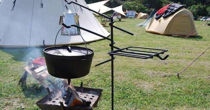 焚き火ハンガーを使ってダッチオーブンとケトルをか焚き火にかける様子