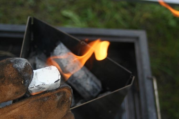 着火剤に火をつけ、チャコスタを上から乗せる写真です。