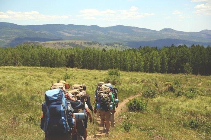 列になって平坦な道を歩く山登りの格好をした人々