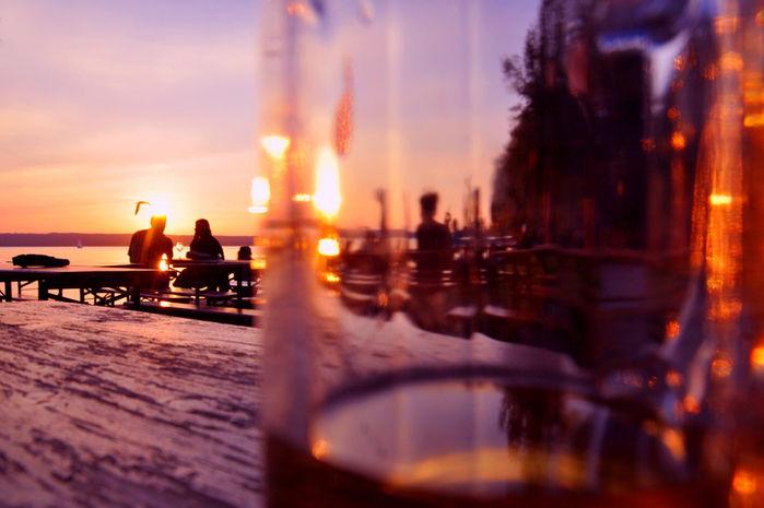 夕焼けを眺めながらお酒を飲むカップル