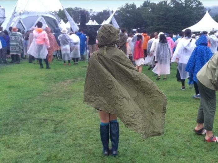 雨の日のフェスでレインコートやポンチョを着る人々
