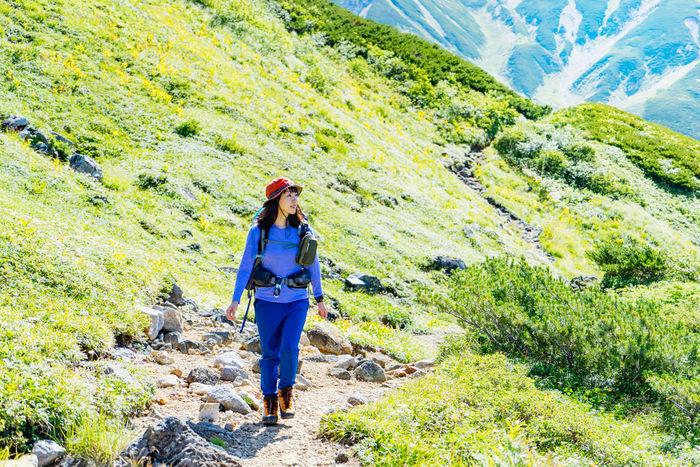 マウンテンパーカーを着て山登りを楽しむ女性