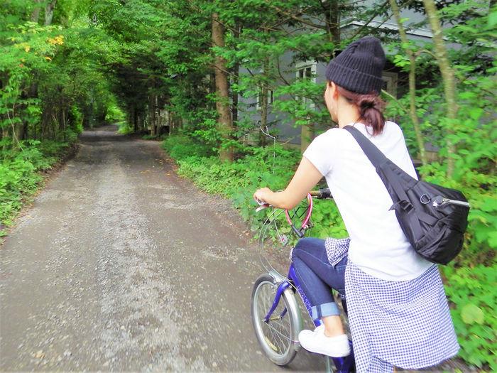 山道をサイクリングする女性の写真
