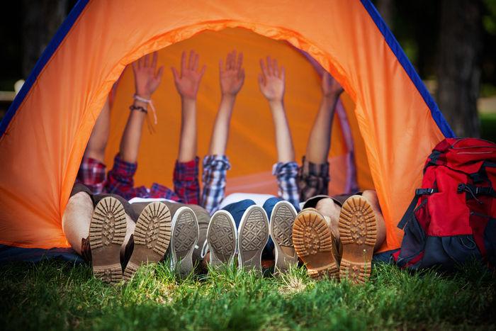 テント内で寝転び手を上に伸ばす人々