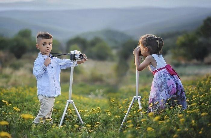 お花畑でカメラで写真を撮る子供達