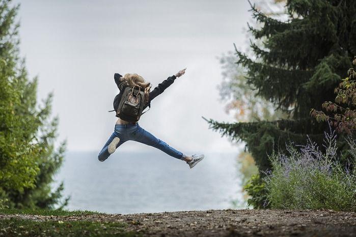 海と自然をバックに飛び跳ねる女性