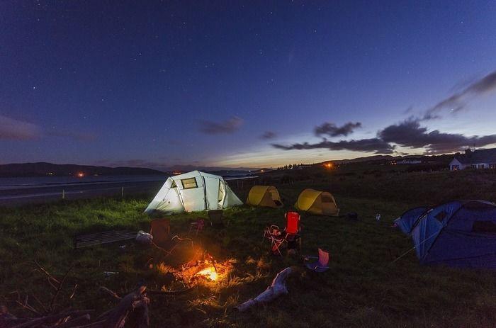 夜のキャンプ場で焚き火をしている様子