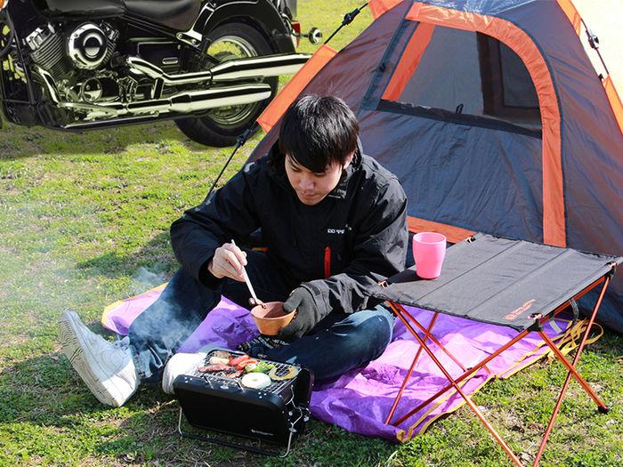 キャンプ場でひとりバーベキューをする男性