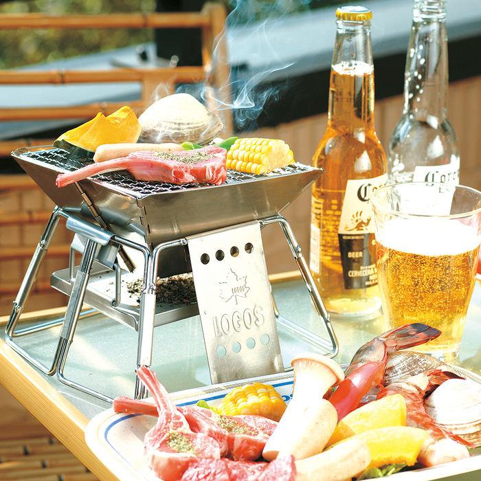 骨つき肉や野菜をバーベキューをしているロゴスのグリルとコロナのビール