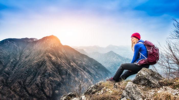 山頂で岩に腰かけている女性