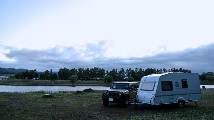 湖のそばに止まっているキャンピングトレーラーを引いている車