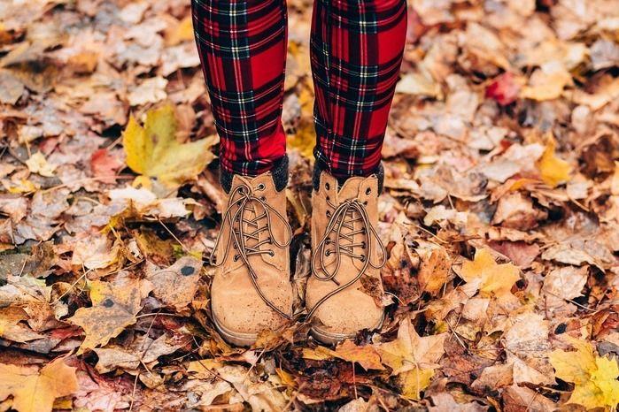 落ち葉を踏むブーツを履いた女性の足元