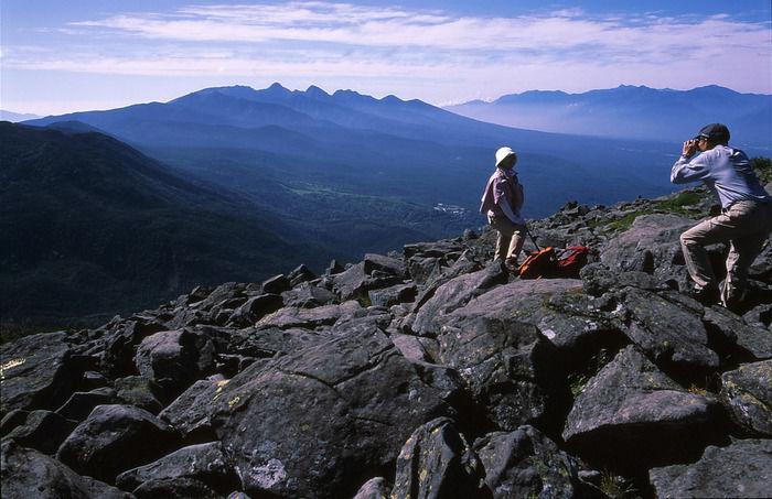 山の岩場に立って写真撮影をする人