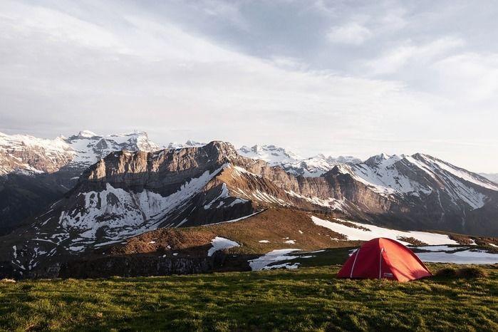 広大な自然の中の1つのテントと背景の険しい山々