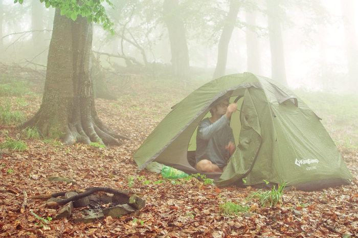 霧の中でテント設営を行う男性