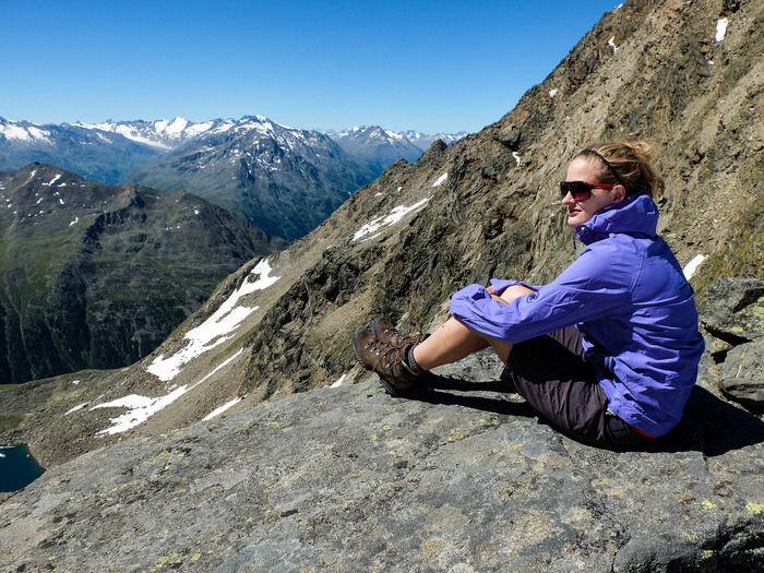 岩に座り風景を眺める女性